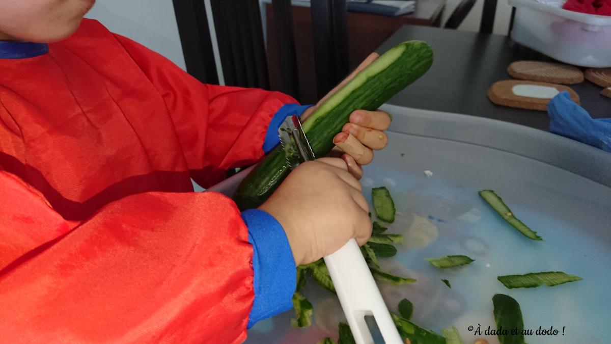 Petite fille épluche un concombre