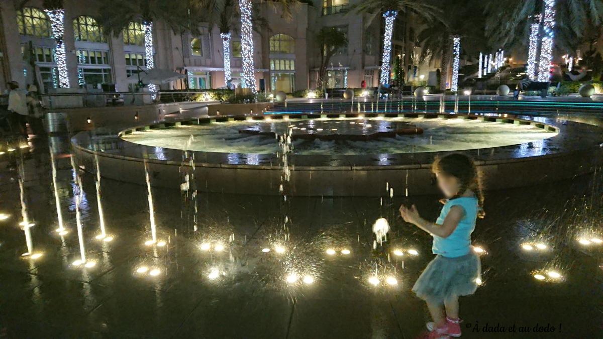 Fillette jouant avec les jets d'eau la nuit