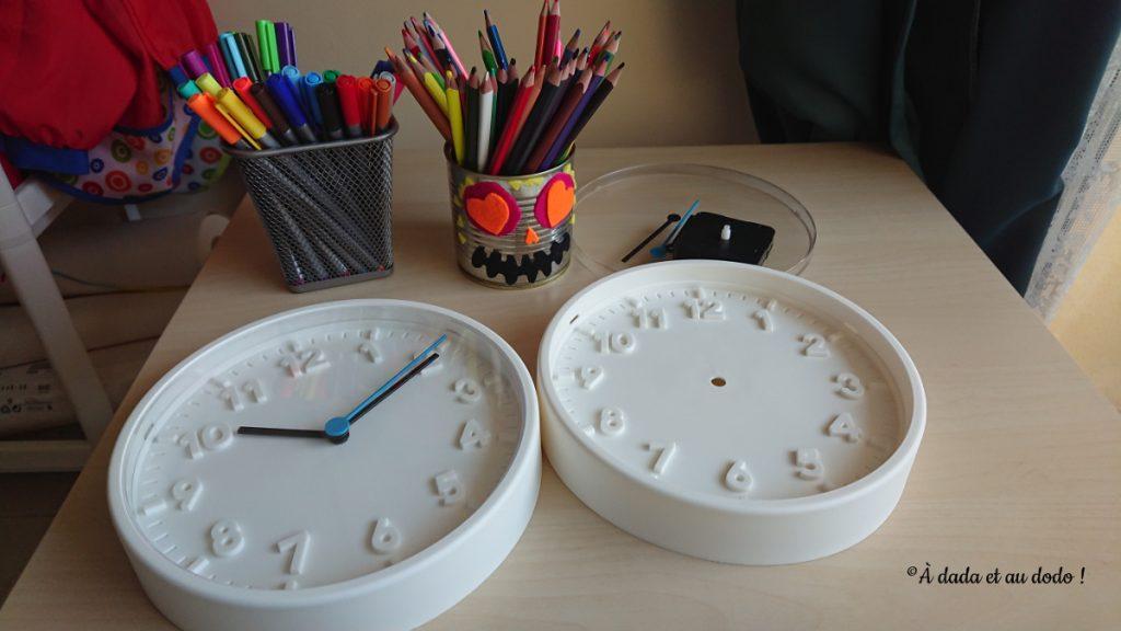 deux horloges, des crayons de couleurs et des feutres